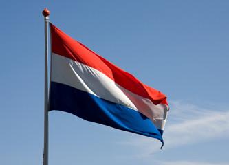 Fluttering Dutch flag over blue sky