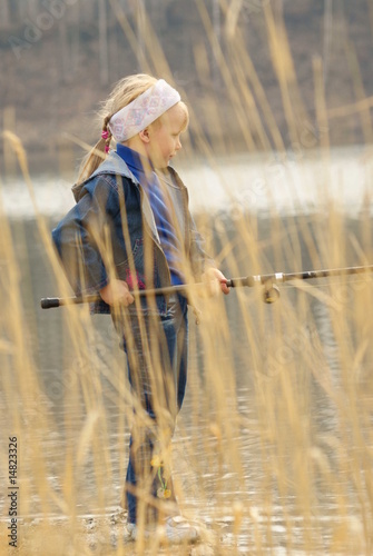 The girl fishs on lake in the spring