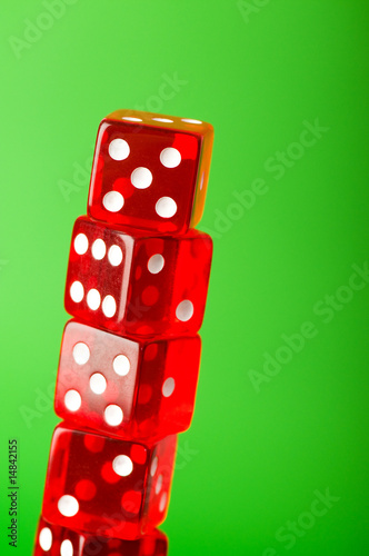 Red dice stack against blurred green background