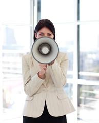 Businesswoman shouting through megaphone to the camera