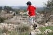 Little boy in red T-shirt and cap jumps from stone outdoors