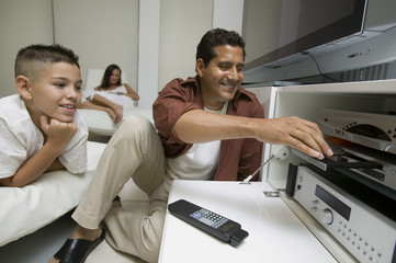Father with son Putting Disc in DVD Player in living room