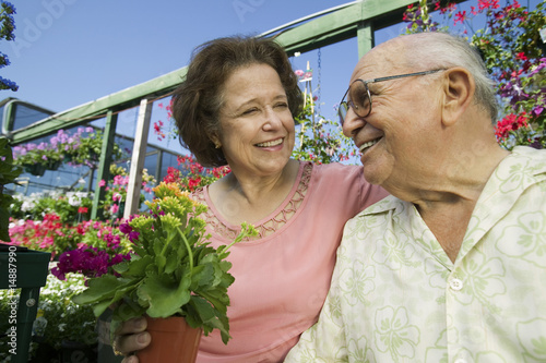 Senior Couple sitting among flowers at plant nursery, close up