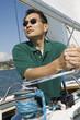 Man raising sail on sailboat
