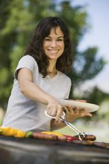 Woman Grilling Food at Park, portrait.