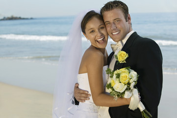 Bride and Groom embracing on beach, portrait