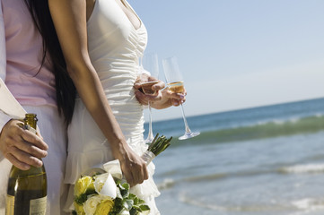 Bride and Groom with champagne at ocean, close-up