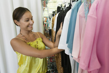 Young Woman Looking Through Clothing Rack in store