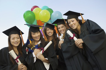 Group of graduates with diplomas and balloons outside, portrait