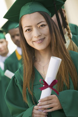 Graduate Holding Diploma outside with others behind, portrait