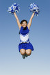 Smiling Cheerleader jumping in mid-air, portrait, low angle view