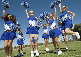 Group of Cheerleaders rising pom-poms, jumping on football field