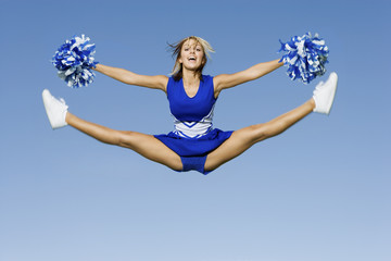 Smiling Cheerleader jumping in mid-air, portrait