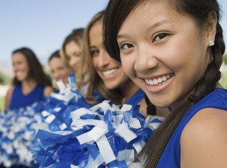 Cheerleaders sitting on bench, portrait