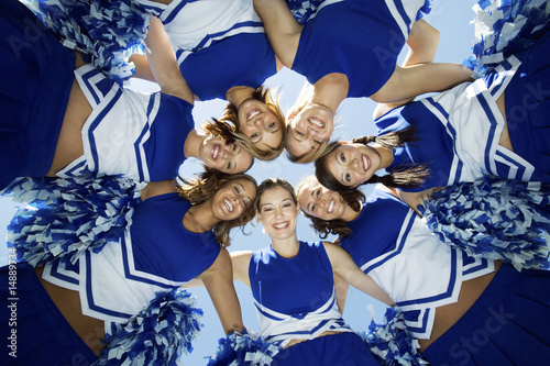 Smiling Cheerleaders standing in circle, portrait, view from below