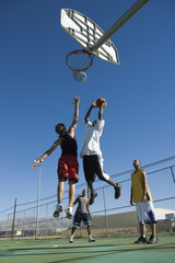 Basketball player, mid-air, shooting ball into hoop while another guards him, low angle view