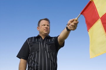Soccer referee holding out penalty flag, portrait