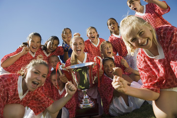 Girls' soccer team 13-17 holding trophy