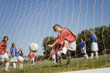 Girl 13-17 scoring with soccer ball