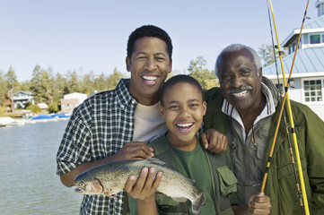 Male members of three generation family showing fish, smiling, portrait