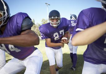Football player running behind linemen on field