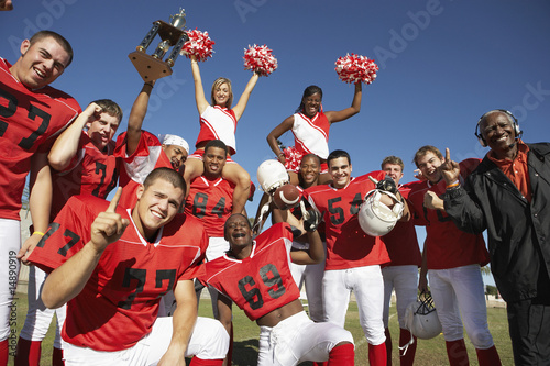 Football players, cheerleaders and coach hoisting trophy, portrait