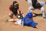 Softball player sliding into home plate