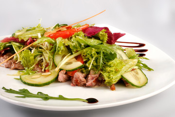A plate of pork with vegetables. File includes clipping path for