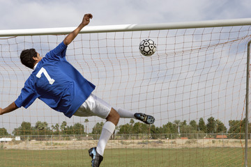 Soccer player scoring goal, back view