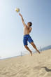Young man jumping, hitting volleyball on beach