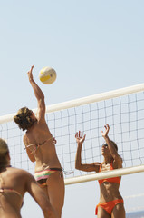 Beach volleyball player jumping to spike volleyball over net, opponent defending