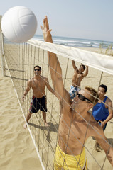 Small group of young men playing volleyball on beach, outstanding the point