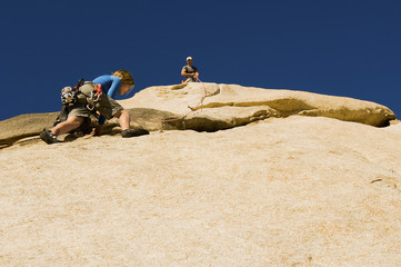 Man assisting woman climbing cliff, low angle view