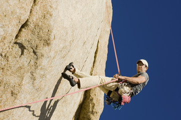 Man Rappelling from Cliff, side view