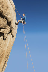 Woman Rappelling on Cliff, side view