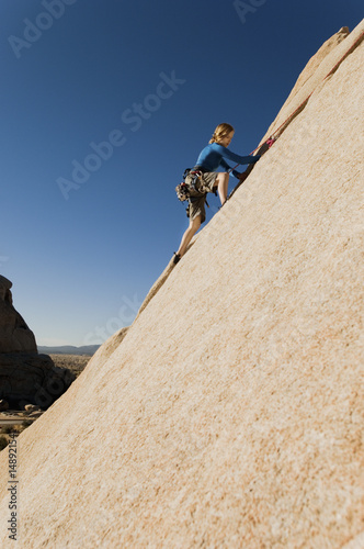 Woman Free Climbing up Cliff