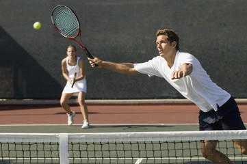Doubles Player stretching, Hitting tennis ball with forehand near net