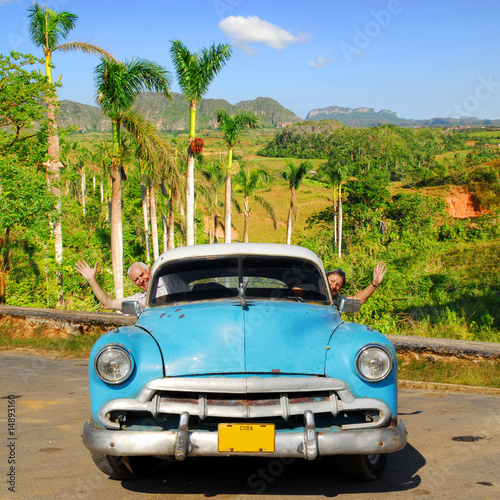 happy european seniors in oldtimer car in vinales, cuba