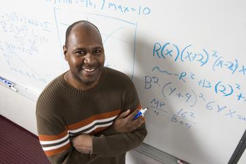 Teacher writing maths equations on whiteboard, portrait