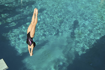 Female diver diving into pool, mid air