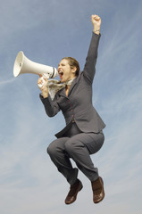 Business woman shouting in bullhorn mid-air outdoors