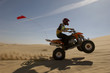 Quad bike rider doing wheelie in desert, side view