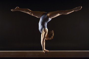 Gymnast 13-15 doing split handstand on balance beam, side view