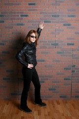 tough looking biker chick leaning against brick wall