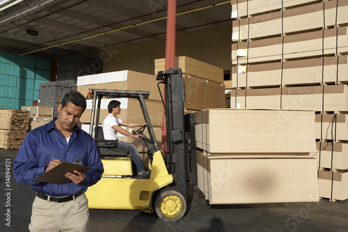 Man with clipboard in front of forklift stacking boxes
