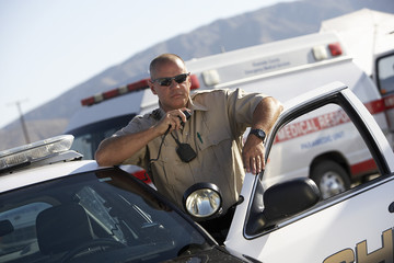 Police officer using two-way radio by police car