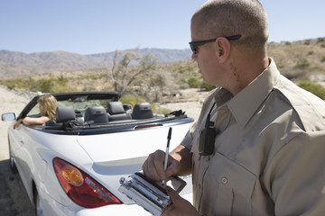 Police officer writing a ticket for a convertible driver