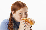 Overweight girl 13-15 eating doughnut, portrait
