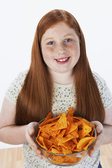 Overweight girl 13-15 holding bowl of snacks, portrait