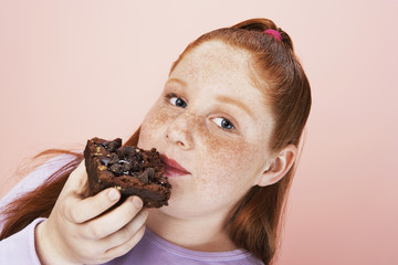 Overweight girl 13-15 Eating brownie, portrait, close-up